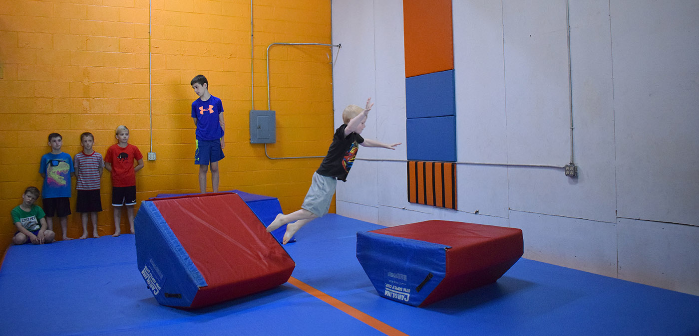 Web header Little boy making jump in obstacle course